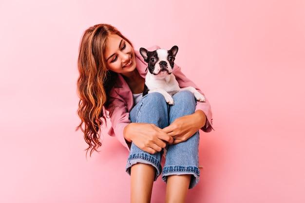 Anmutiges langhaariges mädchen, das hund mit liebe betrachtet. fröhliche dame, die mit französischer bulldogge auf ihren knien aufwirft.