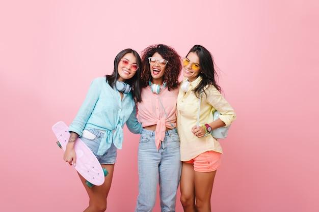 Anmutiges mädchen im gelben hemd mit lederrucksack, der nahe afrikanischer lockiger freund in jeans aufwirft. fröhliche schwarze junge frau in der sonnenbrille, die zwischen europäischen und lateinamerikanischen damen steht.