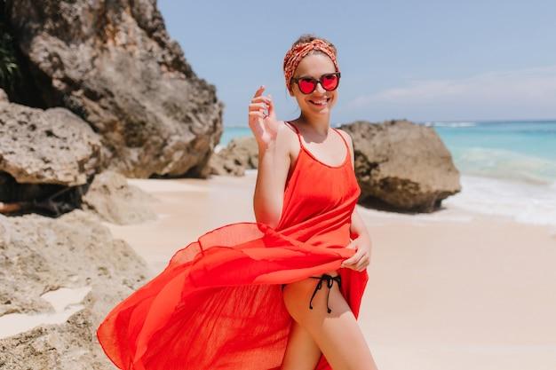 Anmutiges mädchen im roten kleid, das mit hübschem lächeln aufwirft. foto der schlanken gebräunten frau trägt band, das spaß am ozeanresort am wochenende hat.