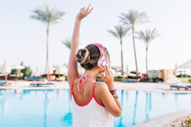 Anmutiges mädchen mit bronzehaut, das weißes trägershirt trägt und mit hand oben nahe dem pool aufwirft