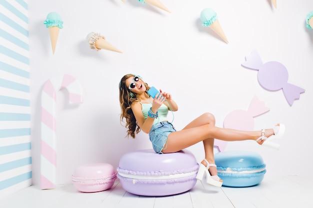Anmutiges mädchen mit dem blauen telefon, das lied singt und lächelt und sich in ihrem dekorierten raum mit mädchenhaftem interieur ausruht. porträt der frohen jungen frau in den kopfhörern, die spaß haben, auf spielzeug lila keks zu sitzen.