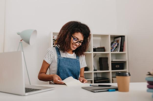 Anmutiges mädchen mit lockigem braunem haar, das dokumente mit hübschem lächeln liest, das in ihrem büro sitzt