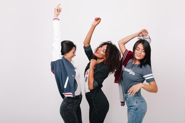 Anmutiges schwarzes weibliches modell, das zwischen lateinamerikanischen und asiatischen freunden tanzt und lieblingslied singt. innenfoto von internationalen studenten, die spaß nach dem gemeinsamen einkauf haben.