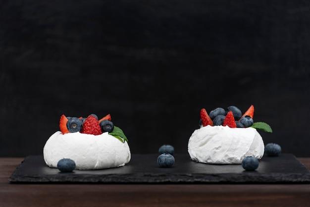 Anna pavlova kuchen auf schwarzem hintergrund. luft baiserkuchen mit frischen erdbeeren und blaubeeren.