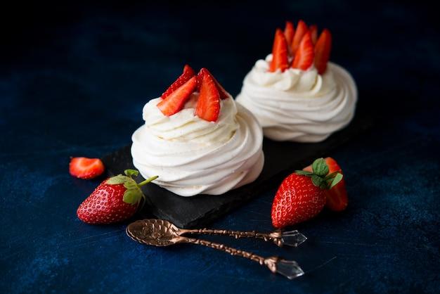 Anna pavlova kuchen mit sahne und frischen erdbeeren auf einem dunklen hintergrund, selektiver fokus