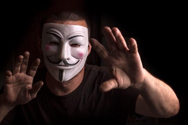 Anonym mit guy fawkes maske mit erhobenen händen.
