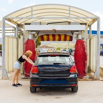 Anonyme frau, die auf auto vor autowäsche sich lehnt