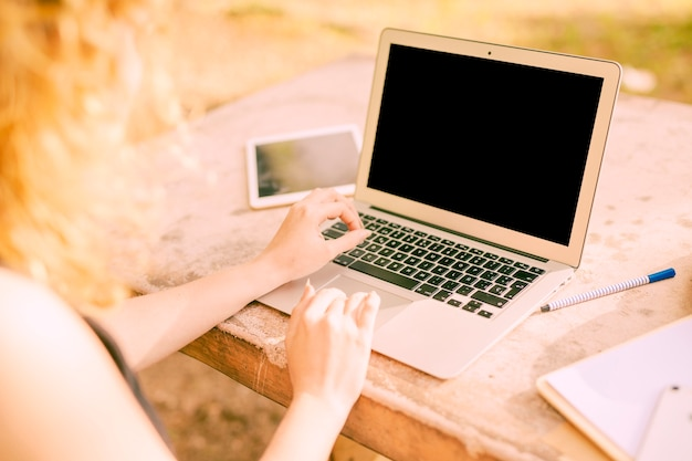 Anonyme frau, die draußen an laptop am schreibtisch arbeitet