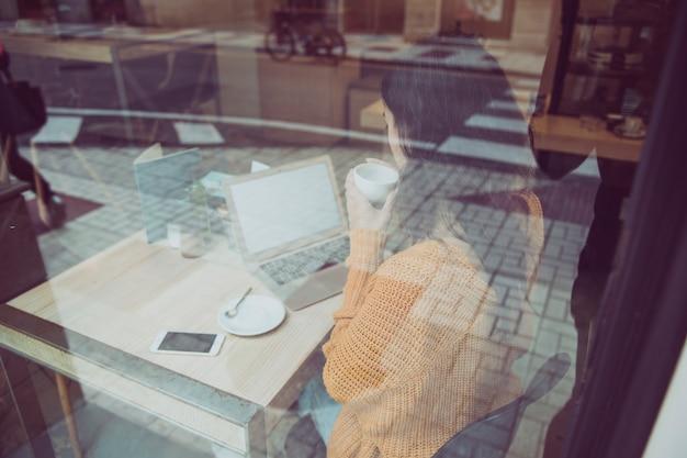 Anonyme frau, die laptop im café trinkt und verwendet