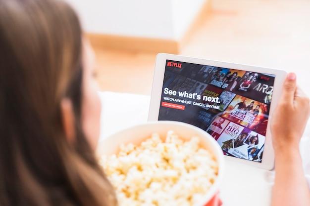 Anonyme frau mit popcorn, der netflix site durchstöbert