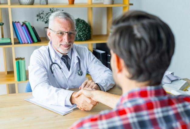 Anonyme geduldige rüttelnde hand von doktor