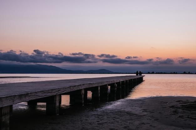 Anonyme personen, die bei sonnenuntergang auf einem pier in der nähe des meeres sitzen