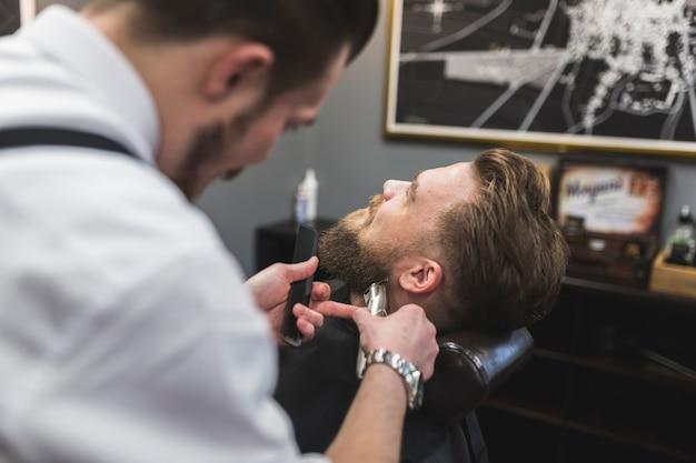 Anonymer barbier, der bart des kunden trimmt