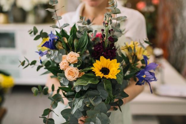 Anonymer florist, der blumenstrauß hält