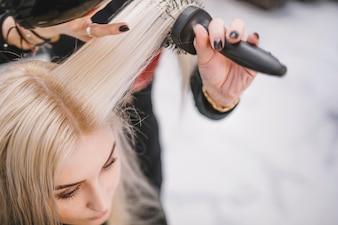 Anonymer Friseur, der Haar des Kunden pflegt