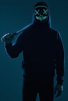 Anonymer krimineller mann mit baseballschläger in einem schwarzen hoodie und in einer neonmaske
