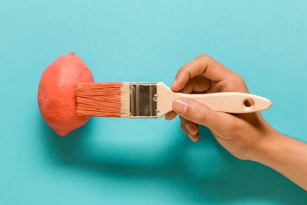 Anonymer künstler, der zitrone in der rosa farbe malt