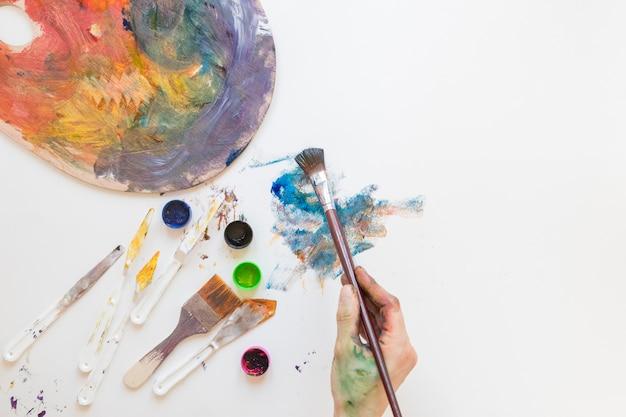 Anonymer maler, der malerpinsel und farbton verwendet
