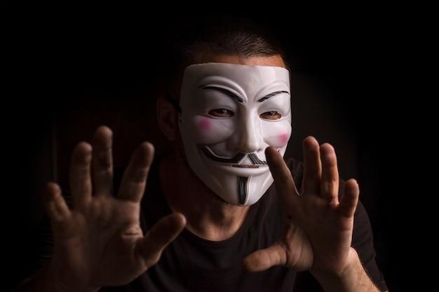 Anonymer mann, der eine guy-fawkes-maske mit erhobenen händen in einem dunklen raum trägt