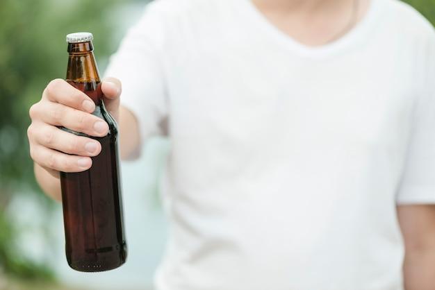 Anonymer mann, der flasche bier zeigt