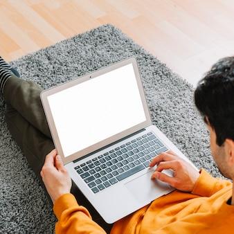 Anonymer mann, der laptop auf teppich verwendet
