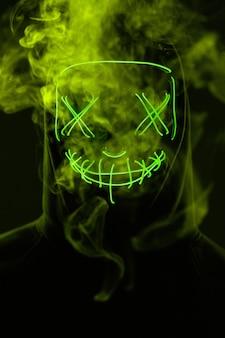 Anonymer mann, der sein gesicht hinter neonmaske in einem farbigen rauch versteckt