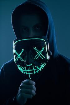 Anonymer mann im schwarzen hoodie, der sein gesicht hinter einer neonmaske versteckt