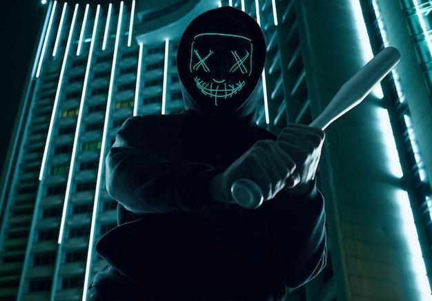 Anonymer mann mit baseballschläger in einem schwarzen kapuzenpulli und einer neonmaske