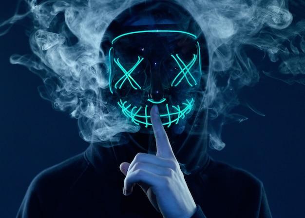 Anonymer mann versteckt sein gesicht hinter neonmaske in einem farbigen rauch
