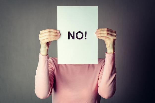 Anonymes frauenbedeckungsgesicht hinter einem weißbuchblatt mit incriprionwort nein