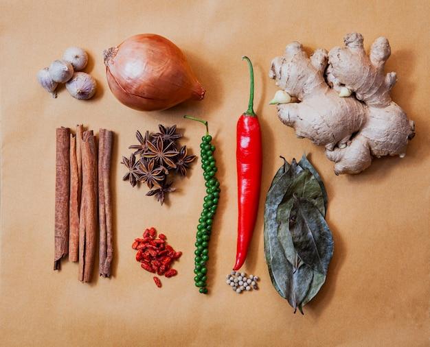 Anordnen des schönen natürlichen asiatischen gewürzs und des gesunden krauts auf erdton papaer hintergrund