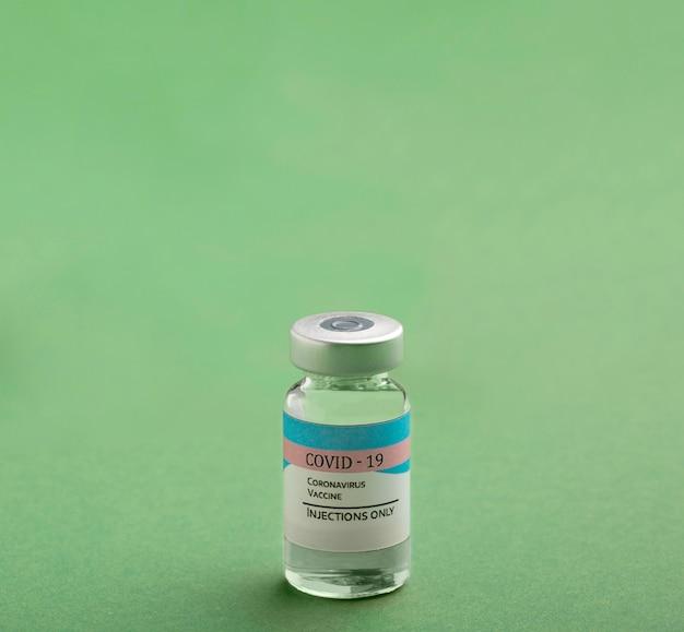 Anordnung der covid19-impfstoffflasche auf grün