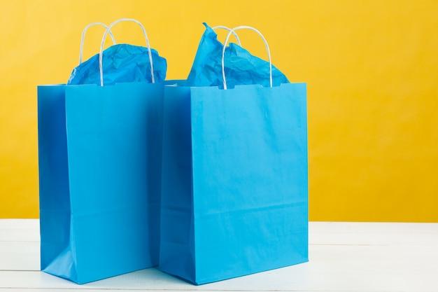 Anordnung der einkaufstaschen auf hellgelbem hintergrund