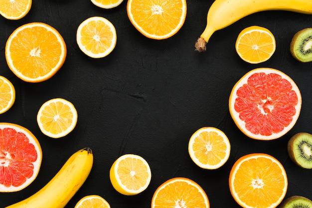 Anordnung der hälfte der tropischen früchte und der ganzen bananen auf schwarzem hintergrund