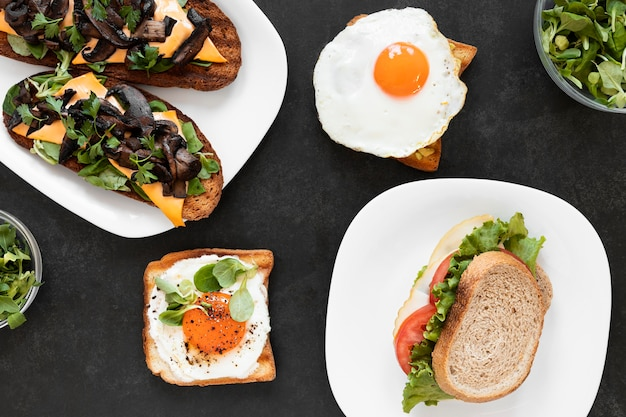 Anordnung der köstlichen sandwiches auf schwarzem hintergrund