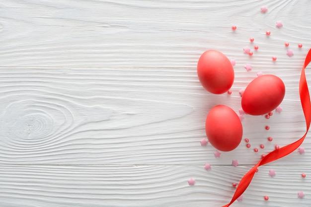 Anordnung der roten ostereier mit band auf holz