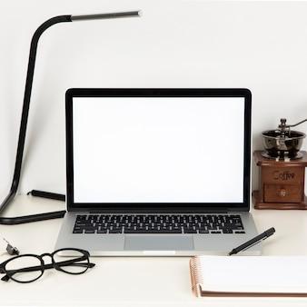 Anordnung der schreibtischelemente mit leerem laptopbildschirm