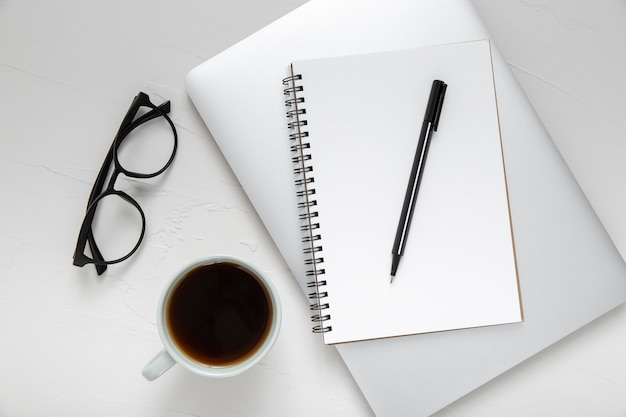 Anordnung der schreibtischelemente mit leerem notizblock auf laptop