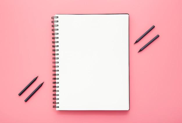 Anordnung der schreibtischelemente mit leerem notizblock auf rosa hintergrund