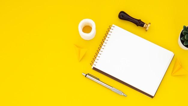 Anordnung der schreibtischelemente mit leerem notizbuch auf gelbem hintergrund