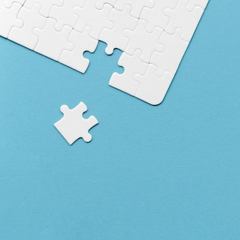 Anordnung der weißen puzzleteile für individualitätskonzept auf blauem hintergrund