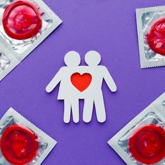 Anordnung des verhütungskonzepts mit roten kondomen und papierpaar