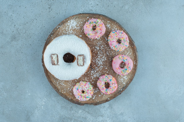 Anordnung eines großen und mehrerer kleiner donuts auf einem holzbrett auf marmor.