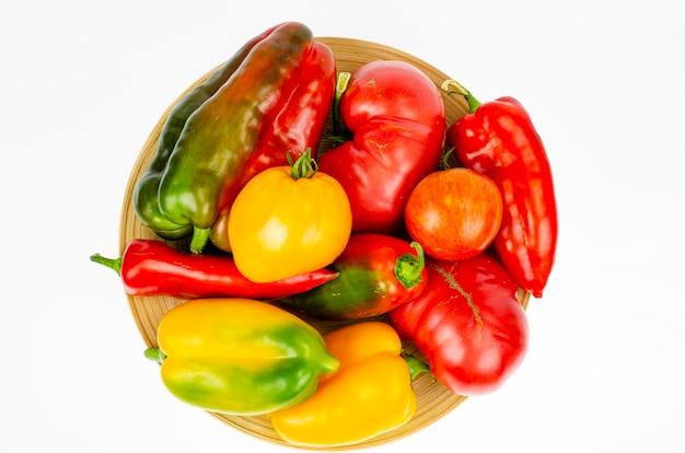 Anordnung für bunte frische sortierte paprika und tomaten in holzplatte auf weißem hintergrund. studiofoto.