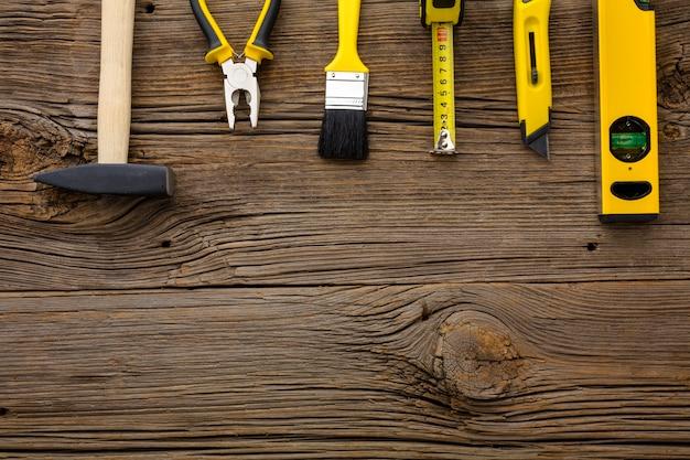 Anordnung für gelbe reparaturwerkzeuge auf hölzernem hintergrund