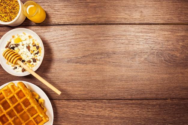 Anordnung für gesundes frühstück auf hölzernem schreibtisch