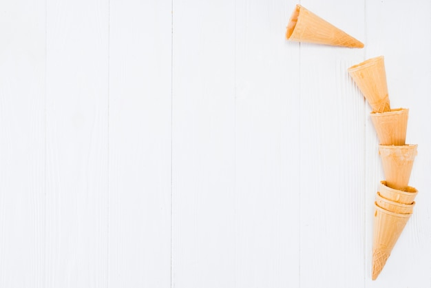 Anordnung für leere waffelkegel für gefrorenen joghurt auf holztisch