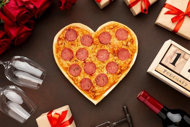 Anordnung für valentinstag mit zentrierter herzförmiger pizza