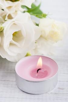 Anordnung für weiße eustomablumen und rosa brennende kerze