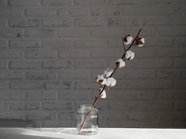 Anordnung mit baumwollblume im glas